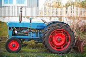 Small Old Blue Tractor With Red Wheels Stands On Grass Nearby Wooden Fence In Norway