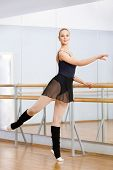 foto of leotards  - Wearing leotard and warmers athlete dances near barre and mirrors in dancing hall - JPG