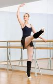 Wearing leotard and warmers ballerina dances near barre and mirrors in studio