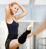 stock photo of ballet barre  - Ballet dancer stretches herself near barre and mirrors in the classroom - JPG