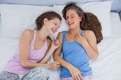 Girls wearing pajamas lying in bed and laughing at slumber party