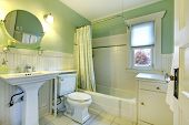 pic of tub  - Mint bathroom with light green curtains tile floor and wood plank wall trim - JPG