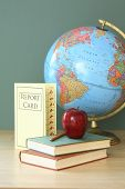education still life with report card, apple, books, pencil, and globe