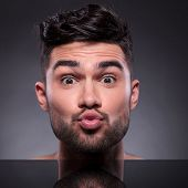 closeup of the head of a young man preparing to kiss you. on a black studio backgroud