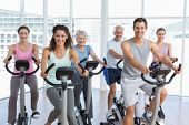 Group portrait of happy people working out at spinning class in gym