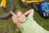 High angle portrait of a relaxed boy gesturing thumbs up at the park