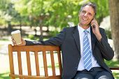 Smiling businessman with disposable cup answering cellphone on park bench