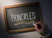 Hand writing the word principles on black chalkboard