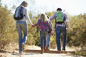 Rear View Of Family Hiking In Countryside Wearing Backpacks