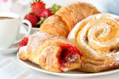 stock photo of continental food  - Continental breakfast with assortment of pastries coffees and fresh strawberries - JPG