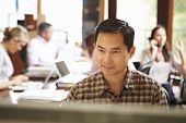 image of pacific islander ethnicity  - Businessman Working At Desk With Meeting In Background - JPG