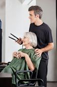 Senior woman with coffee cup and hairdresser holding straightener at beauty parlor