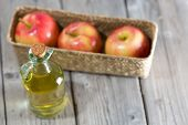 foto of vinegar  - Homemade Vinegar galas apples on a table in a farmhouse