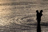 Father hugging his son in the sea silhouetted at sunset in an intimate embrace enjoying the tranquility of the evening with ripples spreading over the surface of the water around them