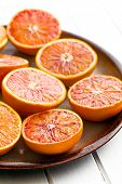 halves of  red oranges on plate