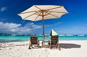 Sun umbrella and beach chairs on tropical coast, Philippines, Boracay