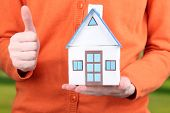 Little paper house in hand close-up, on bright background