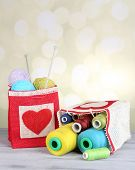 pic of lurex  - Bags with bobbins of colorful thread and woolen balls on wooden table - JPG
