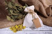 Textile sachet pouch with dried flowers on wooden table, on sackcloth background