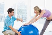 Happy pregnant woman exercising with trainer and ball in a studio