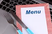 Menu with fork and knife on computer keyboard close up