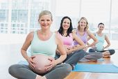 Pregnant women in yoga class sitting on mats touching their bumps in a fitness studio