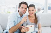 Couple watching movie on the sofa with bowl of popcorn at home in the living room