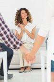 Pleased therapist looking at reconciled couple holding hands at therapy session