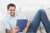 Smiling man relaxing on the couch using his tablet at home in the living room