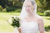 Smiling bride holding flower bouquet while looking away through veil in garden