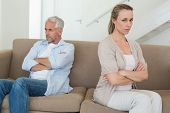 Angry couple sitting on couch not talking to each other at home in the living room
