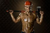stock photo of chopper  - the muscular tired worker chopper man in safety helmet with big heavy ax in hands on netting fence background - JPG