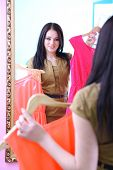 Young beautiful woman trying dresses front of mirror in room