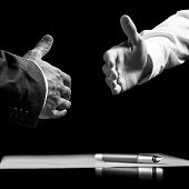 Businessmen About To Shake Hands Over A Signed Contract