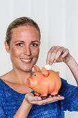stock photo of passbook  - a young woman holding a piggy bank in her hand - JPG