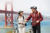 Biking Golden Gate Bridge - couple sightseeing in San Francisco, USA on bicycle. Young couple tourists on bike tour enjoying the view at the famous travel landmark in California, USA.