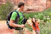 Helping hand - hiking woman getting help on hike smiling happy. Active lifestyle hiker couple traveling. Beautiful smiling mixed race Asian Caucasian female in Zion National Park, Utah, USA.