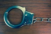stock photo of sadomasochism  - Closeup shot of metallic handcuffs over wooden background - JPG