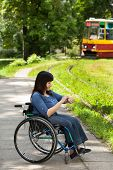Girl On Wheelchair Waiting For Tram