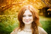 foto of freckle face  - Portrait of redhead girl with blue eyes on nature - JPG