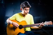 Asian professional guitarist playing acoustic guitar music in recording studio