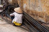 Asian female worker binding steel