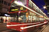 London  red double decker bus at night