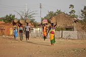 TORIT, SOUTH SUDAN-FEBRUARY 20 2013: Unidentified women carry heavy loads on their heads in Torit, South Sudan