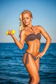 Fitness woman working out on beach in summer. Sporty girl training biceps hard with dumbbells. Sweaty sport caucasian female sportswoman