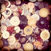 High angle closeup of a group of assorted old buttons in an instagram style with vignette. Square format, filling the frame.
