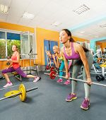 Girls exercising with barbell and weights