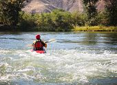 a woman kayaking on a rough river during fall