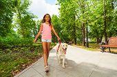 Beautiful teenage girl walking her dogs