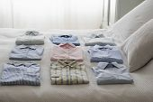 Variety of clean shirts ordered on a bed